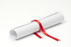 Graduation Scroll. Graduation diploma scroll tied with red ribbon on white background Royalty Free Stock Image