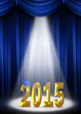 Graduation 2015 in the spotlight. Gold 2015 in the spotlight with blue cap and blue curtain backdrop Royalty Free Stock Images
