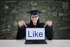 Graduation student showing like on laptop shot in class Stock Images