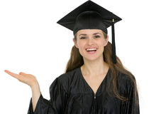 Graduation student showing something on empty hand Stock Photos