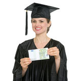 Graduation student woman showing pack of euros Royalty Free Stock Photos