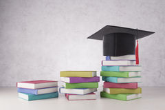 Graduation and success concept. Creative mortarboard and colorful book pile bars placed on concrete background. Graduation and success concept. 3D Rendering Stock Photo
