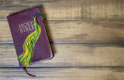 Graduation Tassel on Holy Bible with Wood Background. Yellow and green school or college graduation tassel on a Christian Bible against a distressed wood royalty free stock photos
