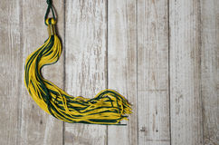 Graduation Tassel on a Wood Background. Yellow and green school or college graduation tassel against a wood plank background stock photos