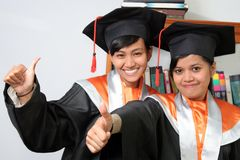 Graduation thumb up. Two graduation girls wirh thumb up Stock Image