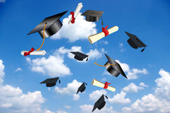 Graduations hats flying on sky Royalty Free Stock Photos