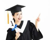 graduazione che mostra diploma e che indica gesto Immagini Stock