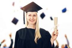Graduazione dell'istituto universitario - abito d'uso della donna che mostra diploma Fotografia Stock Libera da Diritti