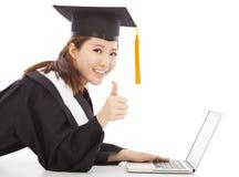 Graduazione femminile facendo uso di un computer portatile e di un pollice su Fotografia Stock