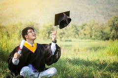 Graduazione: Lo studente si siede e sorride cappello di lancio di graduazione con la D fotografia stock libera da diritti