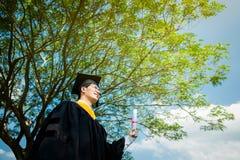 Graduazione: Studente che stanno su e graduazione cer della tenuta di sorriso fotografia stock libera da diritti