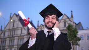 Graduazione: studente felice che chiama gli amici dopo la graduazione archivi video