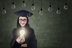 Graduierte gebende gebeleuchtete Birne der attraktiven Frau unter Lampen Lizenzfreie Stockfotos