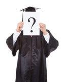 Graduierte Person, die Fragezeichenzeichen hält Stockbild