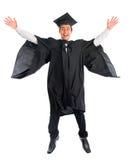 Graduierter Hochschulstudent, der hoch springt Stockbild