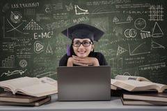 Graduiertes Denken der glücklichen Frau unter Verwendung des Laptops an der Klasse Stockfotografie