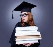 Graduiertes Mädchen im Umhang mit Büchern Lizenzfreie Stockfotografie