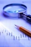 Graf, förstoringsglas och blyertspenna Arkivfoton