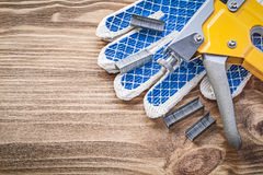 Graffette dei guanti protettivi della pistola della graffetta sul bordo di legno Immagine Stock Libera da Diritti