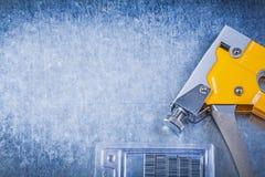 Graffette gialle del cromo della pistola della cucitrice meccanica del tacker sulla b metallica graffiata Fotografia Stock