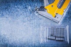 Graffette gialle del cromo della pistola della cucitrice meccanica sul backgrou metallico graffiato Fotografie Stock