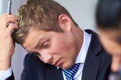 Graffiatura preoccupata e sollecitata dell'uomo d'affari la sua testa Immagini Stock