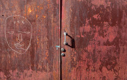 Graffit and peeling paint on old red steel door. Red door and handle with peeling paint and face drawn in white pen with the word fix Stock Photo