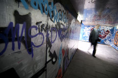 Graffiti. A man walk in a tunnel with graffiti Stock Image