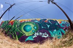 Graffiti. Spray painted fence in an urban area with electrical poles and wires Royalty Free Stock Photos