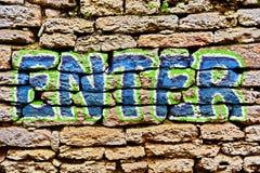 Enter Graffiti. Word enter graffiti painted on a brick wall stock photos