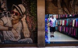 Graffiti art, Gothic Quarter, Barcelona, Spain. Shopkeeper standing in open doorway next to graffiti art in Gothic Quarter, Barcelona, Spain Royalty Free Stock Photo