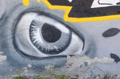 Graffiti art on the street wall in the city showing the painted eye on the gray concrete background.