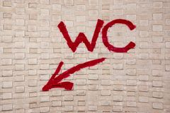Graffiti Art Urban Wall Sign WC With Arrow Stock Image