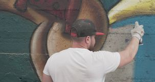 Graffiti artist with aerosol spray bottle. Painting on the wall stock footage