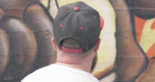 Graffiti artist with aerosol spray bottle. Painting on the wall stock video footage