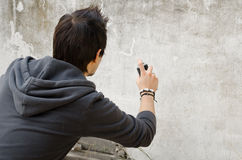 Graffiti artist holding spray can. Graffiti artist about to start spraying a wall, copy space available Royalty Free Stock Photo