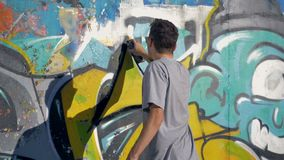 Graffiti artist is painting a black triangle on the yellow letter. 4k stock video footage