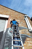 Graffiti artist paints the building wall Stock Images