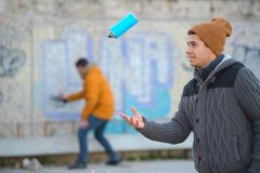 Graffiti artist playing with spraying can Stock Images