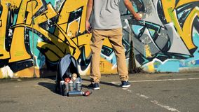A graffiti artist prepares to use a yellow paint can. A graffitist shakes a spray paint before use in back view stock footage