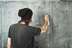 Graffiti artist spraying the wall. Graffiti artist in black clothes spraying the wall Royalty Free Stock Images