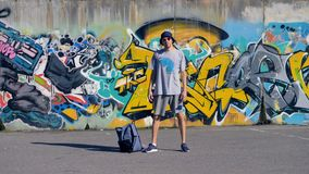 A graffiti artist stands still near his work. A graffitist stands still near his backpack and a painted wall stock video footage