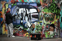 Graffiti artist at work. Creating new images on a wall, London Royalty Free Stock Photos
