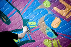 Graffiti Artist At Work. Spraying on a textured brick wall downtown Auckland Stock Photo