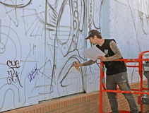 Graffiti Artist. At work using spray paint to draw his painting on a wall at Asbury Park,NJ Stock Photos