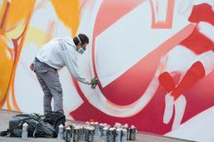 Graffiti artist works on his creation. RUSSIA, MOSCOW - APRIL 18: Unidentified graffiti artist works on his creation for the celebration on the 80th anniversary Stock Photo