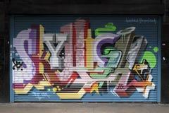 Graffiti auf closedup Shops im Verminderungseinkaufssäulengang St George `` gehen in Croydon stockbilder