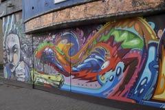 Graffiti auf closedup Shops im Verminderungseinkaufssäulengang St George `` gehen in Croydon lizenzfreie stockbilder