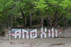 Graffiti auf dem Strand vor Bäumen lizenzfreies stockfoto