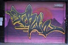 Graffiti auf einem closedup Shop im Verminderungseinkaufssäulengang St George `` gehen in Croydon stockfotos